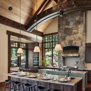Foto på ett rustikt u-kök, med en undermonterad diskho, granitbänkskiva, grått stänkskydd, stänkskydd i kalk, integrerade vitvaror, mörkt trägolv, flera köksöar, brunt golv, skåp i shakerstil och grå skåp