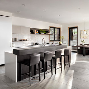 Contemporary open concept kitchen ideas - Inspiration for a contemporary galley gray floor open concept kitchen remodel in Other with flat-panel cabinets, white cabinets, white backsplash and an island