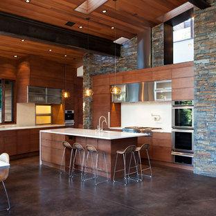 Modern inredning av ett stort kök, med en undermonterad diskho, släta luckor, skåp i mellenmörkt trä, bänkskiva i onyx, vitt stänkskydd, stänkskydd i porslinskakel, rostfria vitvaror, betonggolv och en köksö