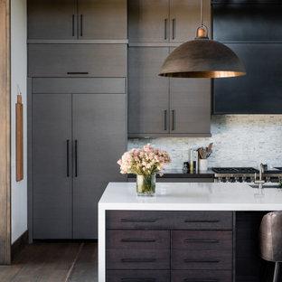 Offene, Zweizeilige, Große Moderne Küche mit Waschbecken, flächenbündigen Schrankfronten, braunen Schränken, Küchenrückwand in Grau, Rückwand aus Stäbchenfliesen, Elektrogeräten mit Frontblende, braunem Holzboden, Kücheninsel, braunem Boden und weißer Arbeitsplatte in Sacramento