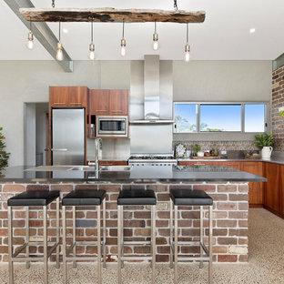 Cette photo montre une cuisine rétro en L avec un évier 3 bacs, un placard à porte plane, des portes de placard en bois brun, un plan de travail en inox, une crédence métallisée, un électroménager en acier inoxydable, un sol en terrazzo et un îlot central.