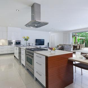 Diseño de cocina en L, minimalista, grande, abierta, con fregadero bajoencimera, armarios con paneles lisos, puertas de armario blancas, salpicadero blanco, electrodomésticos de acero inoxidable, una isla y suelo de linóleo