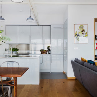 This is an example of a large contemporary open plan kitchen in London with flat-panel cabinets, white cabinets, stainless steel worktops, metallic splashback, medium hardwood flooring, an island and an integrated sink.