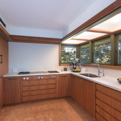 Inspiration for a small mid-century modern u-shaped medium tone wood floor and brown floor enclosed kitchen remodel in Los Angeles with an undermount sink, flat-panel cabinets, medium tone wood cabinets, solid surface countertops, white backsplash, paneled appliances, no island and white countertops