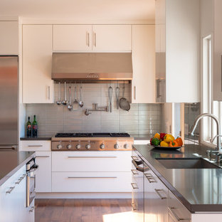 Contemporary kitchen designs - Example of a trendy l-shaped medium tone wood floor kitchen design in Los Angeles with gray backsplash, an island, a single-bowl sink, flat-panel cabinets, white cabinets, solid surface countertops, glass tile backsplash and stainless steel appliances