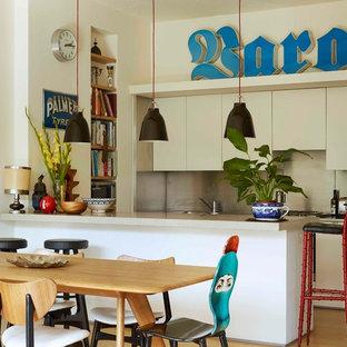 ロンドンの大きいエクレクティックスタイルのおしゃれなキッチン (ドロップインシンク、フラットパネル扉のキャビネット、白いキャビネット、コンクリートカウンター、メタリックのキッチンパネル、パネルと同色の調理設備、無垢フローリング、茶色い床、グレーのキッチンカウンター) の写真