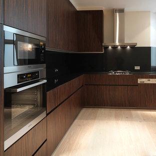 ロンドンの小さいアジアンスタイルのおしゃれなキッチン (一体型シンク、フラットパネル扉のキャビネット、茶色いキャビネット、御影石カウンター、黒いキッチンパネル、ガラス板のキッチンパネル、パネルと同色の調理設備、ラミネートの床) の写真