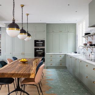 Diseño de cocina en L, clásica renovada, abierta, con armarios estilo shaker, puertas de armario verdes, salpicadero de mármol, electrodomésticos negros, suelo verde y encimeras blancas