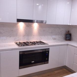 Exempel på ett modernt kök, med marmorbänkskiva, vitt stänkskydd, stänkskydd i sten, släta luckor, vita skåp, rostfria vitvaror, ljust trägolv och en köksö