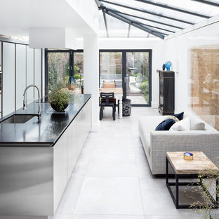 Inspiration for a large industrial galley open plan kitchen in London with an island, a submerged sink, flat-panel cabinets, white floors and black worktops.