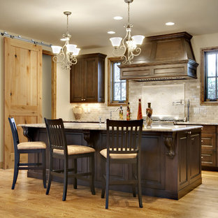 Mid-sized elegant u-shaped light wood floor and beige floor eat-in kitchen photo in Tampa with shaker cabinets, dark wood cabinets, laminate countertops, beige backsplash, stainless steel appliances and an island