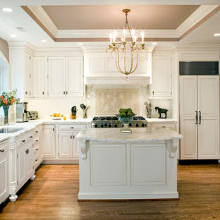 Kitchen - traditional l-shaped medium tone wood floor kitchen idea in DC Metro with an undermount sink, raised-panel cabinets, white cabinets, beige backsplash, paneled appliances and an island