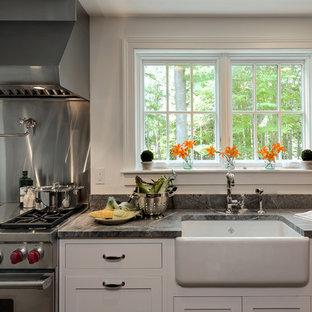 Lantlig inredning av ett kök, med en rustik diskho, skåp i shakerstil, vita skåp, granitbänkskiva, stänkskydd med metallisk yta, stänkskydd i metallkakel och rostfria vitvaror