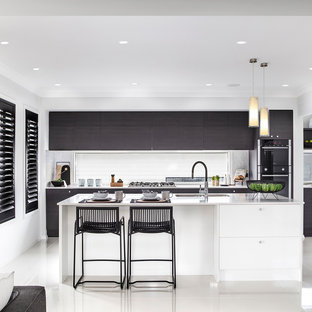 Inspiration for a mid-sized contemporary galley kitchen pantry in Wollongong with an undermount sink, shaker cabinets, dark wood cabinets, marble benchtops, glass sheet splashback, black appliances, ceramic floors, with island, white floor and white benchtop.