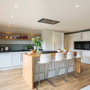 Transitional kitchen in London with shaker cabinets, white cabinets, grey splashback, subway tile splashback, black appliances, light hardwood floors and with island.