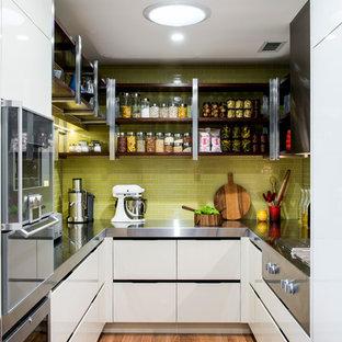 Foto på ett avskilt, litet funkis u-kök, med släta luckor, vita skåp, bänkskiva i rostfritt stål, grönt stänkskydd och mellanmörkt trägolv