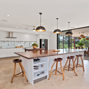 Contemporary kitchen in Perth with flat-panel cabinets, white cabinets, white splashback, glass sheet splashback, stainless steel appliances, beige floor, white benchtop and multiple islands.