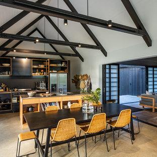 Zweizeilige Moderne Wohnküche mit integriertem Waschbecken, offenen Schränken, schwarzen Schränken, Edelstahl-Arbeitsplatte, Küchenrückwand in Schwarz, Küchengeräten aus Edelstahl, Betonboden, Kücheninsel, grauem Boden und grauer Arbeitsplatte in Auckland