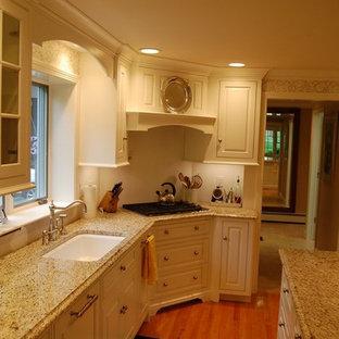 Mittelgroße Klassische Wohnküche in U-Form mit Unterbauwaschbecken, weißen Schränken, Granit-Arbeitsplatte, Küchenrückwand in Weiß, Kücheninsel, profilierten Schrankfronten, Rückwand aus Metrofliesen, weißen Elektrogeräten und hellem Holzboden in Bridgeport