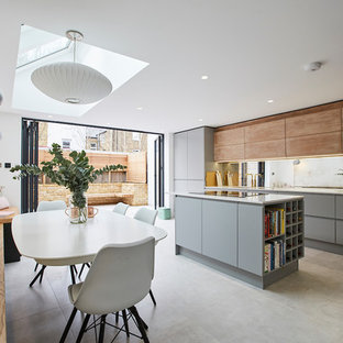 Photo of a medium sized contemporary open plan kitchen in London with an integrated sink, composite countertops, mirror splashback, integrated appliances, ceramic flooring, an island, grey floors, white worktops, flat-panel cabinets and grey cabinets.