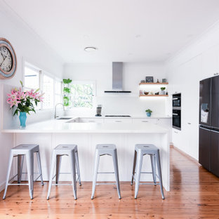 Design ideas for a mid-sized contemporary u-shaped kitchen in Sydney with an undermount sink, shaker cabinets, white cabinets, quartz benchtops, white splashback, stone slab splashback, black appliances, medium hardwood floors, a peninsula, brown floor and white benchtop.