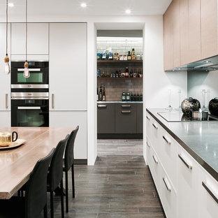 Foto på ett funkis kök och matrum, med släta luckor, vita skåp, rostfria vitvaror, granitbänkskiva, stänkskydd med metallisk yta, spegel som stänkskydd, klinkergolv i keramik och brunt golv