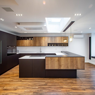 Inspiration for a medium sized contemporary u-shaped kitchen/diner in London with a built-in sink, beaded cabinets, black cabinets, quartz worktops, white splashback, ceramic splashback, black appliances, dark hardwood flooring, an island, brown floors and black worktops.