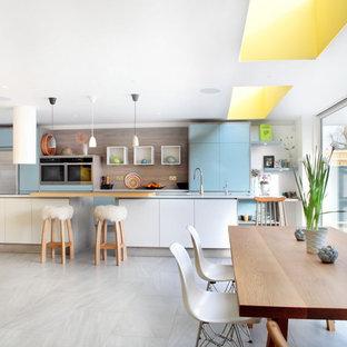 Пример оригинального дизайна: большая линейная кухня-гостиная в современном стиле с плоскими фасадами, столешницей из кварцита, фартуком из дерева, техникой из нержавеющей стали, полом из керамогранита, островом, монолитной раковиной и серыми фасадами