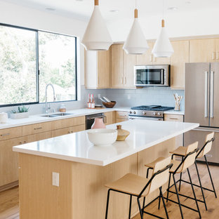 Contemporary kitchen inspiration - Example of a trendy l-shaped medium tone wood floor and brown floor kitchen design in Los Angeles with a double-bowl sink, flat-panel cabinets, light wood cabinets, stainless steel appliances, an island and white countertops