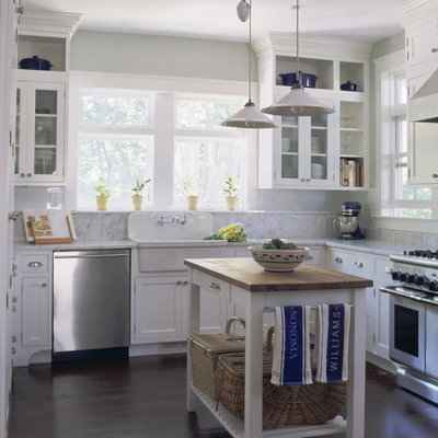 Inspiration for a timeless kitchen remodel in New York with glass-front cabinets, stainless steel appliances and a farmhouse sink