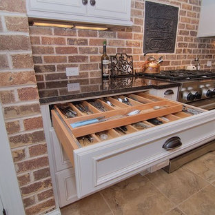 Mid-sized rustic eat-in kitchen photos - Example of a mid-sized mountain style l-shaped travertine floor and beige floor eat-in kitchen design in Charlotte with a farmhouse sink, beaded inset cabinets, white cabinets, granite countertops, red backsplash, brick backsplash, stainless steel appliances and an island