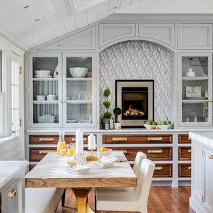 Cette image montre une cuisine américaine marine avec un placard à porte vitrée, des portes de placard grises, une crédence multicolore, un sol en bois brun, un sol marron et un plan de travail blanc.