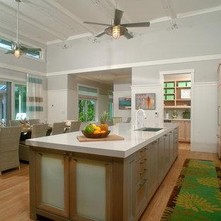 Idéer för att renovera ett stort tropiskt linjärt kök och matrum, med ljust trägolv, brunt golv, en undermonterad diskho, rostfria vitvaror, luckor med infälld panel, skåp i ljust trä, bänkskiva i kvarts och en köksö