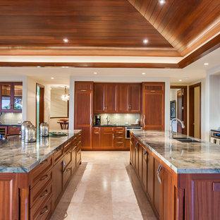 Aménagement d'une grande cuisine exotique avec un placard avec porte à panneau encastré, un plan de travail en quartz, une crédence verte, une crédence en carreau de verre, un électroménager en acier inoxydable, un sol en travertin et 2 îlots.