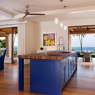 ハワイの中くらいのトロピカルスタイルのおしゃれなキッチン (アンダーカウンターシンク、フラットパネル扉のキャビネット、白いキャビネット、木材カウンター、サブウェイタイルのキッチンパネル、無垢フローリング、ベージュキッチンパネル、シルバーの調理設備、茶色い床) の写真