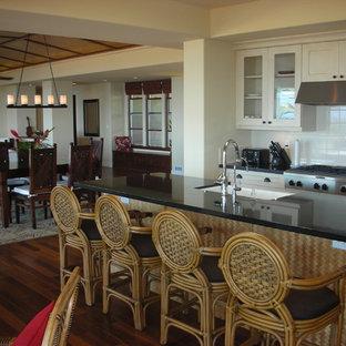 Idées déco pour une cuisine ouverte exotique avec un placard à porte vitrée, un plan de travail en granite et une crédence blanche.