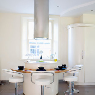 This is an example of a contemporary kitchen/diner in Other with flat-panel cabinets, beige cabinets, wood worktops and brown floors.