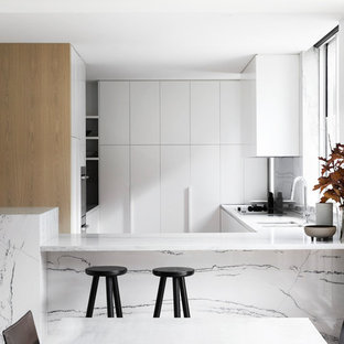 Inspiration for a contemporary u-shaped kitchen in Melbourne with a double-bowl sink, flat-panel cabinets, white cabinets, white splashback, stone slab splashback, a peninsula and white benchtop.
