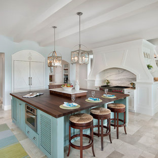 Beach style kitchen designs - Example of a coastal kitchen design in Miami with paneled appliances, an island, shaker cabinets, white cabinets and white backsplash