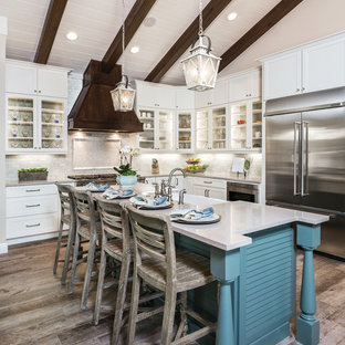 Transitional kitchen ideas - Kitchen - transitional l-shaped medium tone wood floor kitchen idea in Miami with a farmhouse sink, glass-front cabinets, white cabinets, quartz countertops, stainless steel appliances, an island and beige backsplash