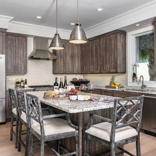Rustic kitchen inspiration - Inspiration for a rustic l-shaped light wood floor kitchen remodel in Miami with an undermount sink, shaker cabinets, distressed cabinets, granite countertops, beige backsplash, subway tile backsplash, stainless steel appliances and an island