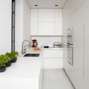 Idée de décoration pour une cuisine minimaliste en L fermée avec un évier encastré, un placard à porte plane, des portes de placard blanches, un électroménager encastrable et une crédence blanche.