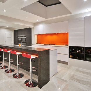 This is an example of a medium sized contemporary galley kitchen in London with a submerged sink, flat-panel cabinets, white cabinets, quartz worktops, orange splashback, glass sheet splashback, black appliances, porcelain flooring, an island, beige floors and white worktops.