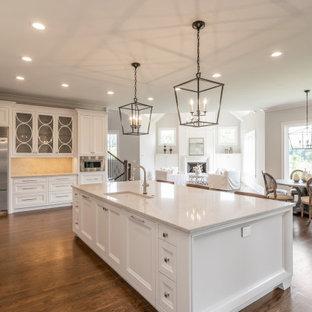 アトランタの広いカントリー風おしゃれなキッチン (アンダーカウンターシンク、落し込みパネル扉のキャビネット、白いキャビネット、クオーツストーンカウンター、ベージュキッチンパネル、石スラブのキッチンパネル、シルバーの調理設備、濃色無垢フローリング、茶色い床、ベージュのキッチンカウンター) の写真