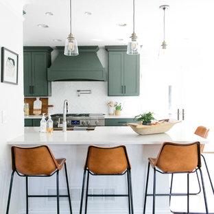 デンバーの中サイズのトランジショナルスタイルのおしゃれなキッチン (エプロンフロントシンク、シェーカースタイル扉のキャビネット、緑のキャビネット、クオーツストーンカウンター、白いキッチンパネル、レンガのキッチンパネル、シルバーの調理設備の、無垢フローリング、茶色い床、白いキッチンカウンター) の写真