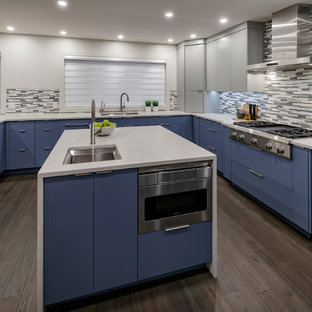 Photo of a large modern u-shaped eat-in kitchen in Calgary with an undermount sink, flat-panel cabinets, blue cabinets, quartzite benchtops, multi-coloured splashback, glass tile splashback, stainless steel appliances, dark hardwood floors, multiple islands, brown floor and white benchtop.