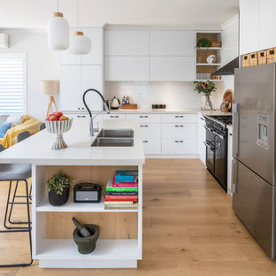 This is an example of a modern kitchen in Perth with flat-panel cabinets, white cabinets, quartz benchtops, white splashback, subway tile splashback, medium hardwood floors, with island, white benchtop, a double-bowl sink, stainless steel appliances and brown floor.