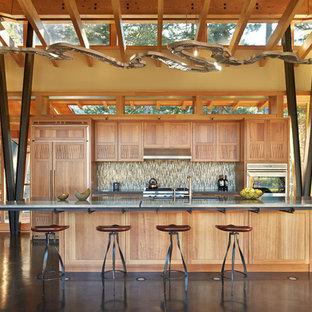 Diseño de cocina de galera, contemporánea, grande, abierta, con fregadero bajoencimera, puertas de armario de madera oscura, encimera de vidrio, salpicadero de azulejos de vidrio, electrodomésticos con paneles, suelo de cemento y una isla