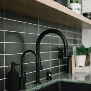 ロサンゼルスの中サイズのモダンスタイルのおしゃれなキッチン (アンダーカウンターシンク、フラットパネル扉のキャビネット、中間色木目調キャビネット、ライムストーンカウンター、黒いキッチンパネル、サブウェイタイルのキッチンパネル、パネルと同色の調理設備、コンクリートの床、アイランドなし、グレーの床、緑のキッチンカウンター) の写真