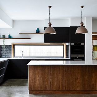 This is an example of a contemporary kitchen in Other with flat-panel cabinets, black cabinets, window splashback, concrete floors, with island and grey floor.
